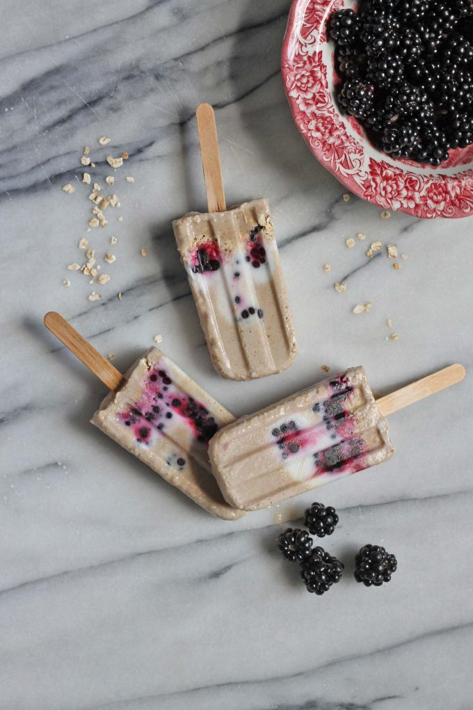 Popsicles on a marble board next to bowl of blackberries.