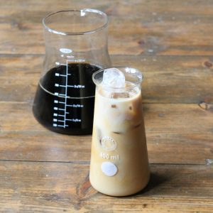 A glass of iced coffee in front of a carafe of coffee.