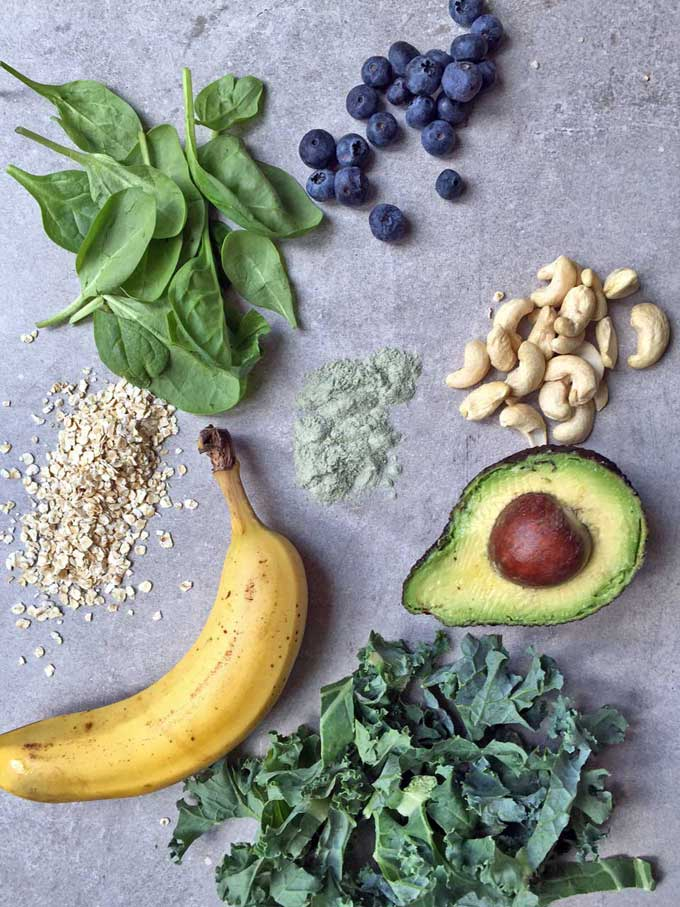 Flat lay of ingredients: spinach, blueberries, oats, banana, cashews, avocado, kale.