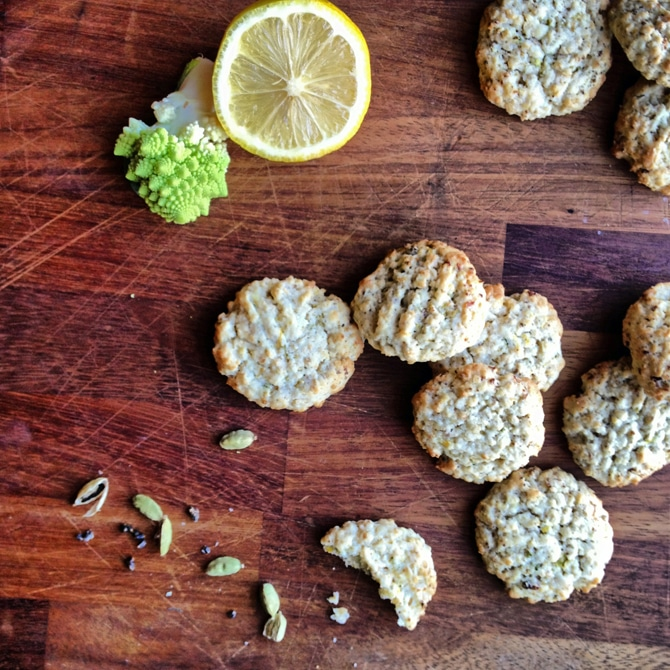 Romanesco Cardamom Lemon Cookies on a wooden board with lemon and romanesco next to them.
