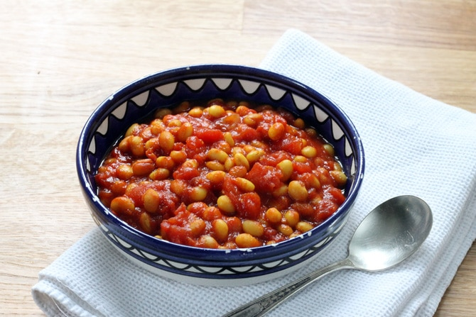 A blue bowl full of homemade baked beans with turmeric.