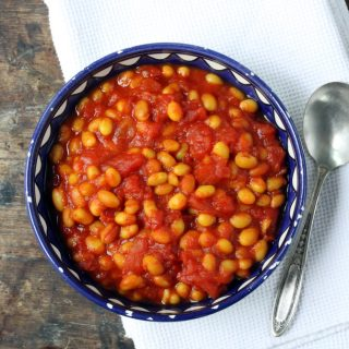 Bowl of baked beans on a table.