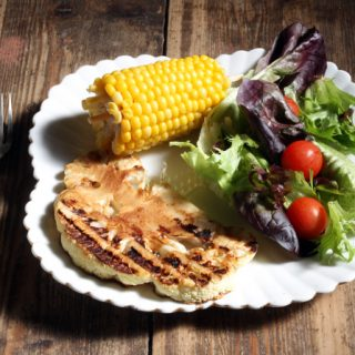 A table with a plate of cauliflower steak, salad and corn on the cob.