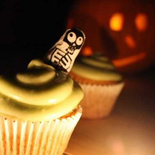 A cupcake with a lit jack o'lantern in the background.