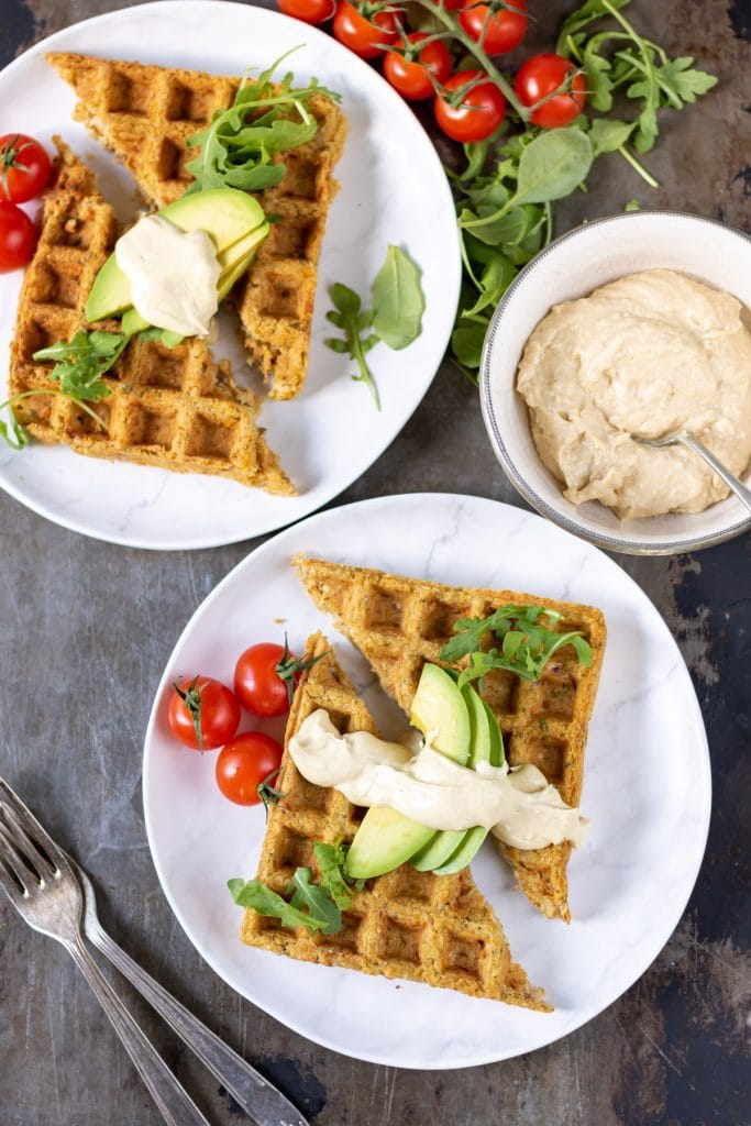 Two plates with falafel waffles, tomatoes, avocado and hummus.