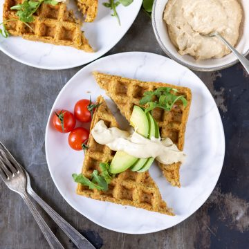 A table with plates of waffled falafels topped with avocado and hummus.