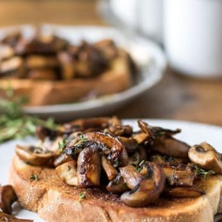 Mushrooms on toast with garlic and thyme. Shown as a vegetarian or vegan breakfast, brunch, lunch or dinner recipe.