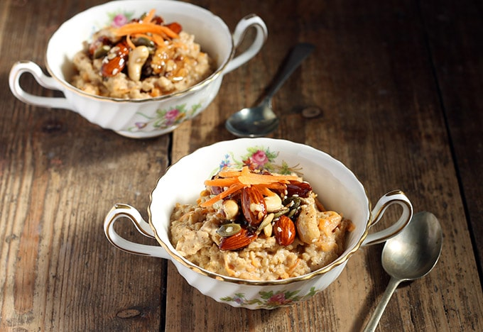 Two bowls of oatmeal topped with nuts.