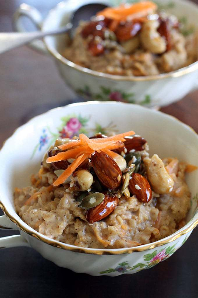 Close up of a bowl of oatmeal topped with candied nuts and grated carrot.