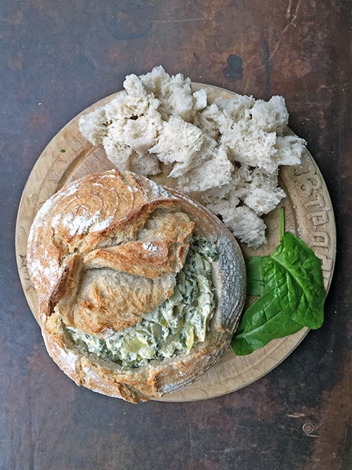 Hot Spinach and Artichoke Dip in a Sourdough Bread Bowl on a wooden board