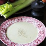 Bowl of blue cheese soup in front of celery sticks.