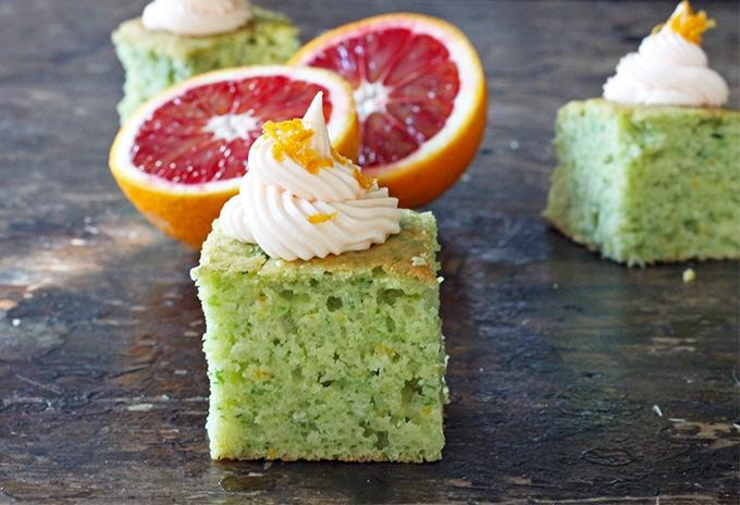 A slice of cake next to a cut orange.