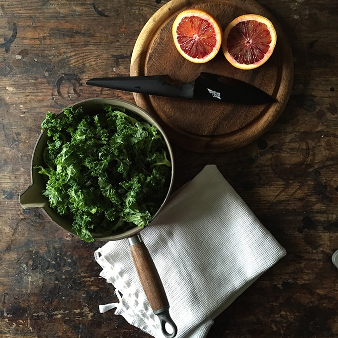 A table with oranges and a bowl of kale.