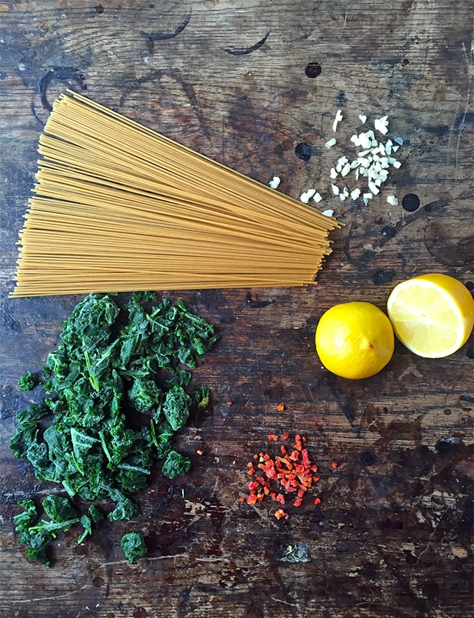 A table with spaghetti, garlic, kale, lemon and chilli.