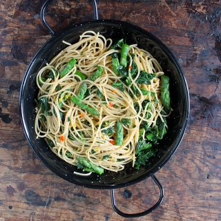 A bowl of spaghetti with asparagus, chilli and lemon on a wooden table.