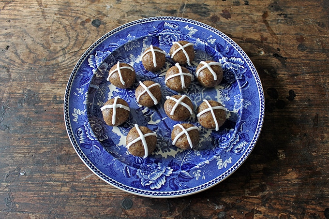 A plate full of bliss balls with icing crosses on them.