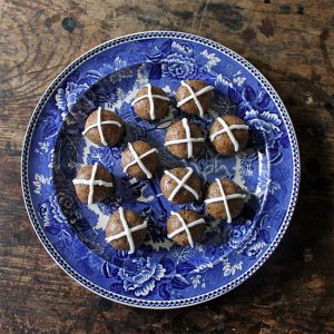 Hot cross balls on a vintage plate on a wooden table.