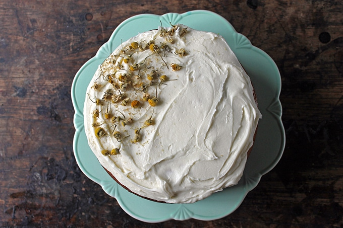 Chamomile Cake decorated on half the top with chamomile tea buds. Shown on a vintage cake stand.