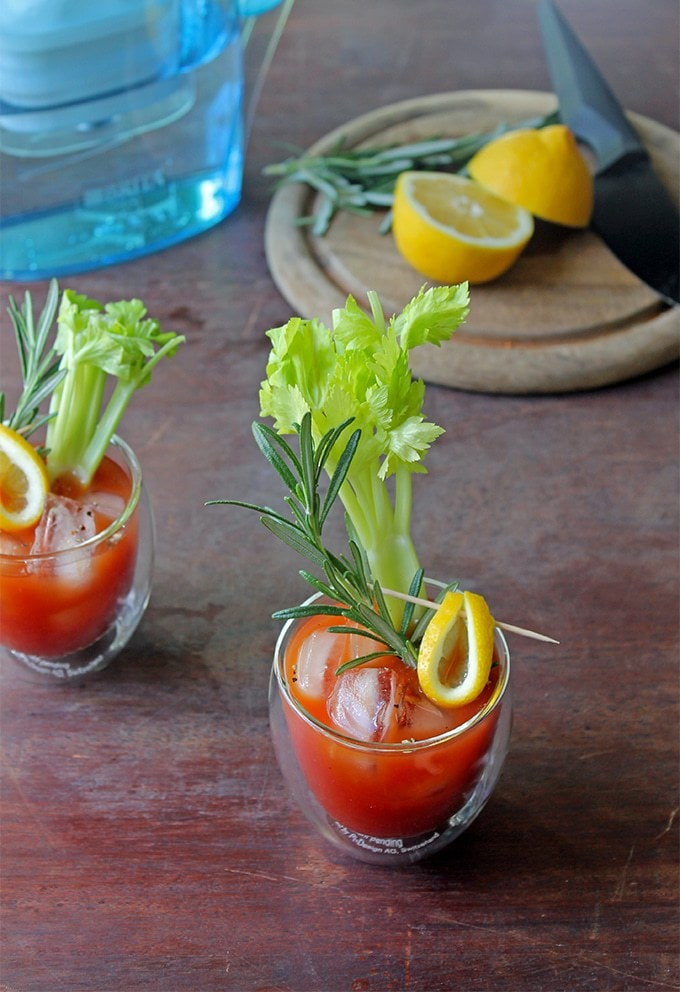 Shot of two Alcohol-Free Coffee Bloody Mary in glasses with celery and rosemary sticking out