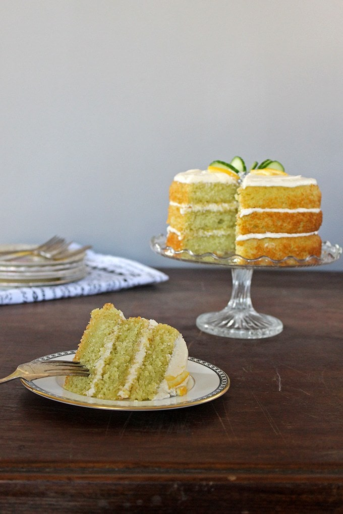 A slice of Lemon and Cucumber Cake with Gin Icing taken from the cake, which is in the background