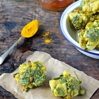 Cauliflower and Spinach Pakora recipe - a bowl of vegan gluten free vegetable pakora next to a teaspoon of turmeric and sauces.