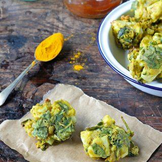 Cauliflower and Spinach Pakora recipe - a bowl of vegan gluten free vegetable pakora next to a teaspoon of turmeric and sauces.