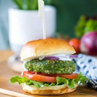 A pea spinach burger in a bun with lettuce, tomato, red onion and mayo. The vegan burger patty is bright green. Get the recipe now.