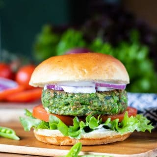 A burger bun with lettuce, tomato, onion, mayo and a bright green vegan burger patty made from spinach and peas.