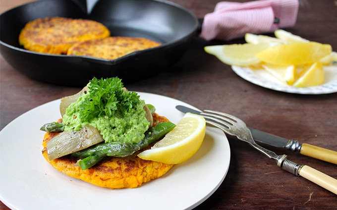 A plate of sweet potato cakes topped with vegetables.