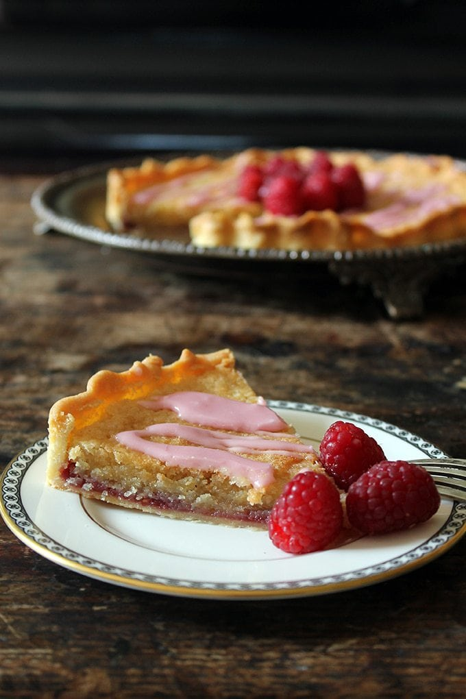 A slice of bakewell tart on a vintage plate - with layers of crisp shortcrust pastry, raspberry jam and almond frangipane with a pink raspberry drizzle and a few fresh raspberries.