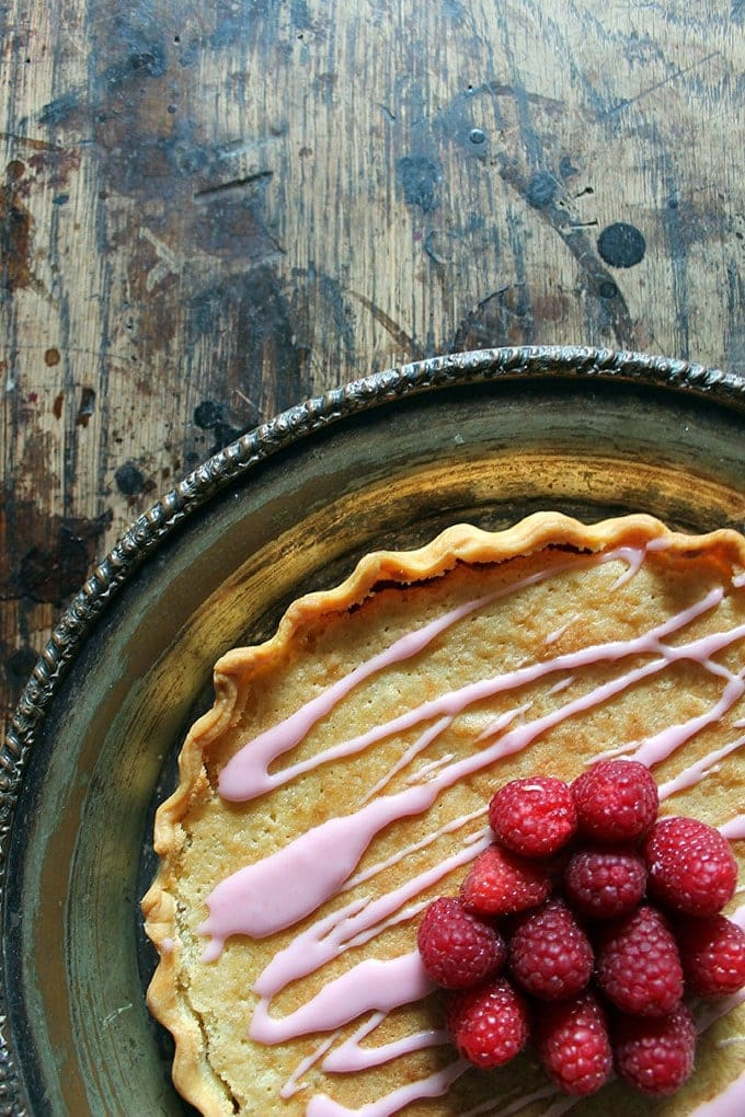 A vintage silver serving tray with a pretty bakewell tart (aka bakewell pudding) on it, with a pink raspberry drizzle and handfull of fresh raspberries.