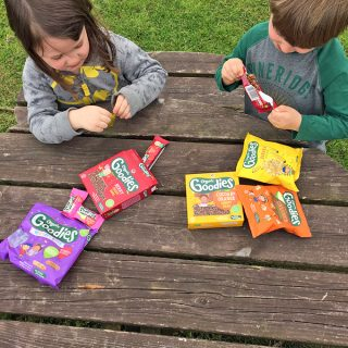 Children opening packets of Organix healthy snacks outdoors on a picnic table.