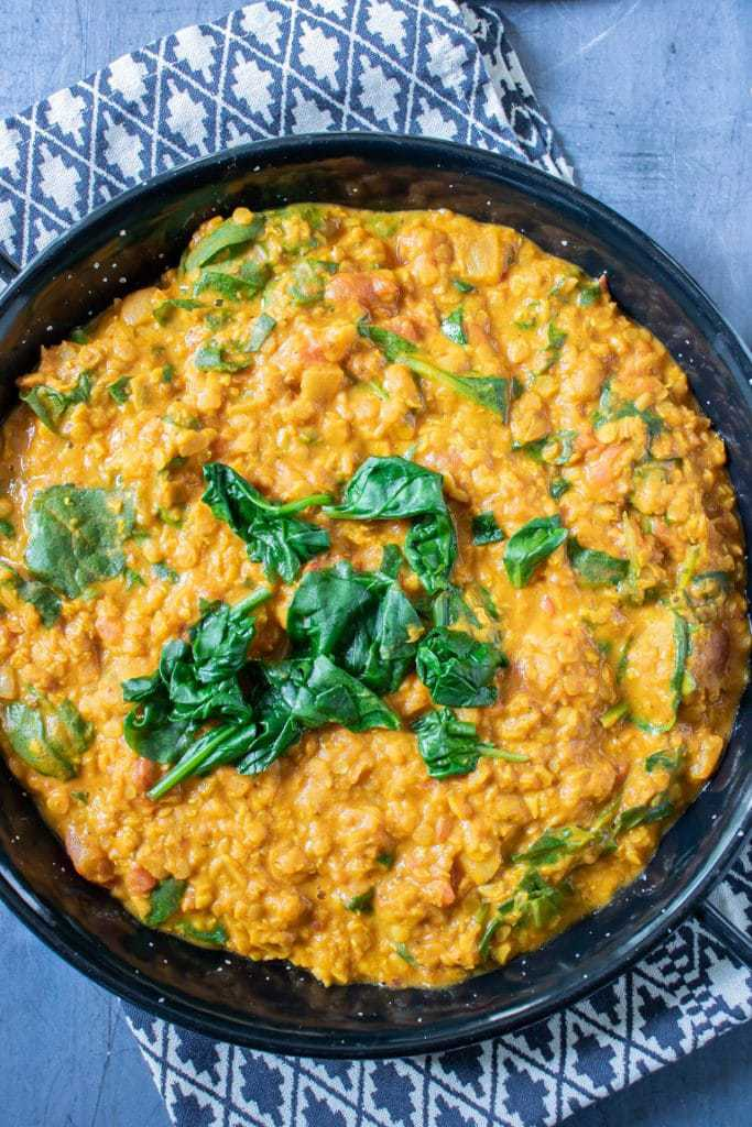 Red lentil dhal in a black dish with a small pile of freshly wilted spinach. Vegan, vegetarian, gluten free recipe.