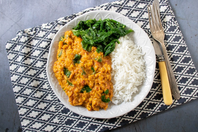 A white plate with rice, spinach and red lentil dhal - a creamy vegetarian, vegan and gluten free curry. On a pattered tea towel with vintage cutlery.
