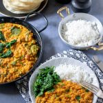 A table with a large dish of red lentil dahl, with a plate of poppadoms, dish of rice and a plate served with dal, rice and spinach. A quick curry that's vegetarian, vegan and gluten free.