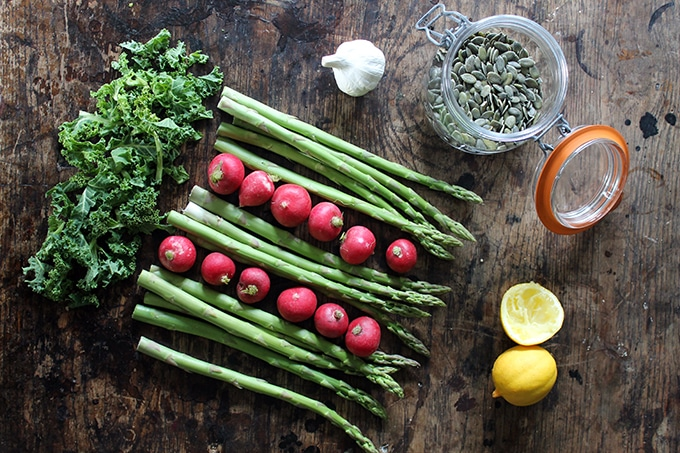A table with radishes, asparagus, kale, lemon and pumpkin seeds.