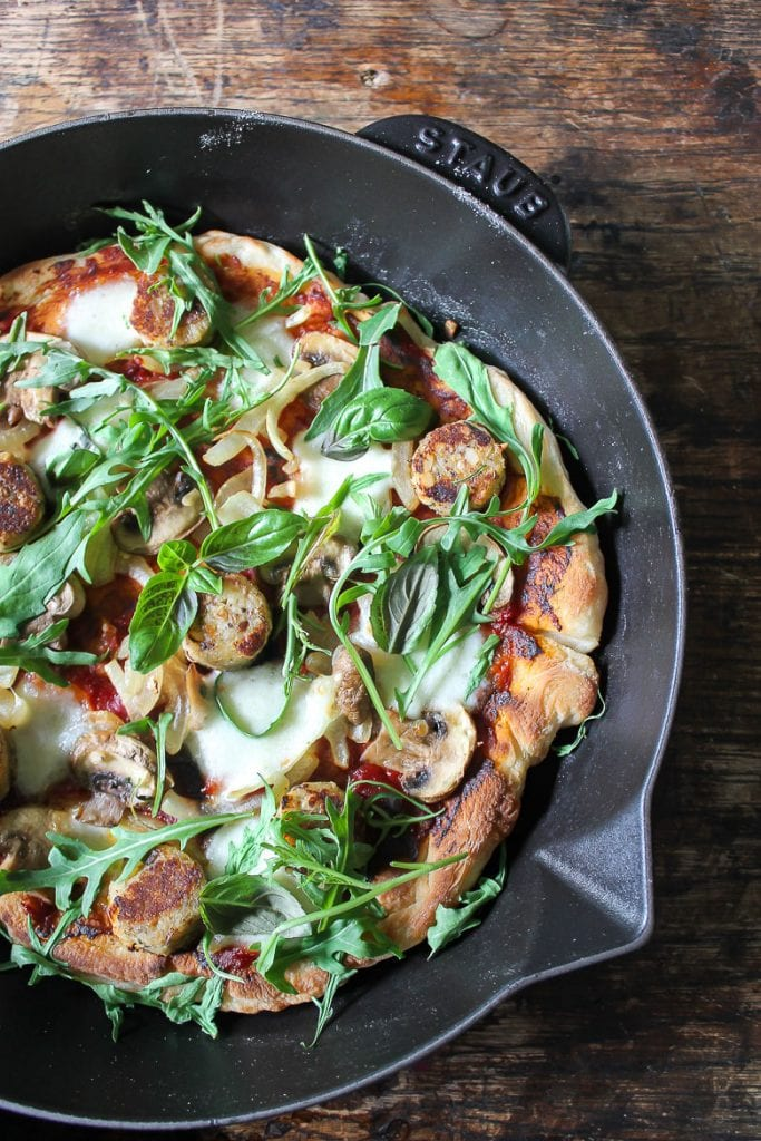 Close up of skillet pizza with toppings on wooden table
