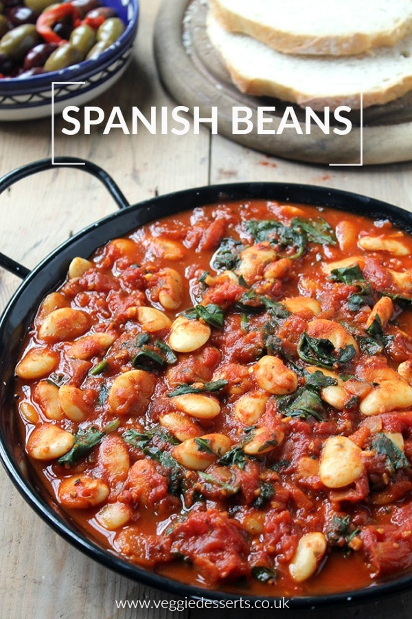 Spanish Beans with tomatoes in a black dish, which can be served as a main meal or tapas. Photographed with bread and olives. Vegan and gluten free recipe.