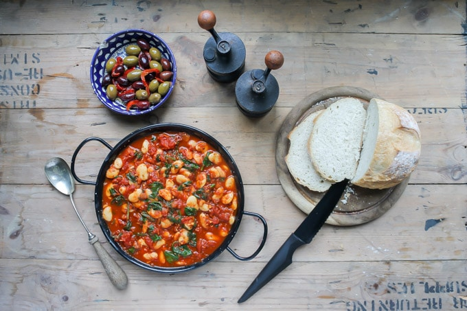 Overhead shot of Spanish Beans and Tomatoes with a dish of olives. A great main dish or tapas.