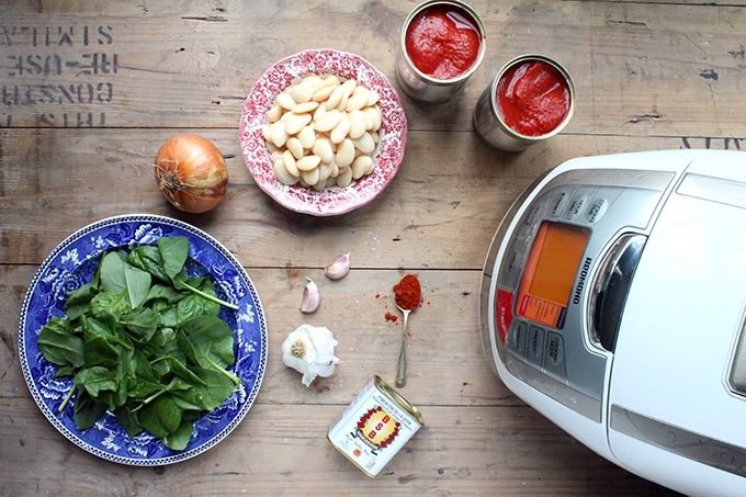 Spanish Beans and Tomatoes - flat lay of ingredients: tinned tomatoes, white beans, onion, spinach, garlic, smoked paprika