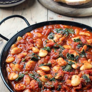 Serving dish of beans in tomatoes.