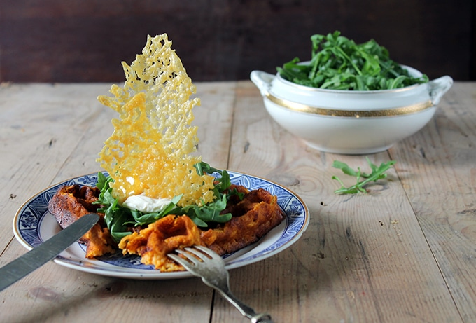 A table with a plate of waffle with spinach and a shard of melted cheddar cheese.