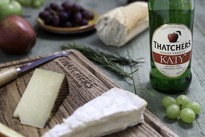 A bottle of cider and a wooden tray with cheeses.