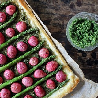 A tart with radishes and asparagus on a wooden table.