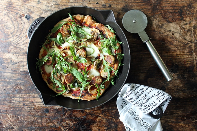Pizza in a skillet with pizza cutter and tea towel.