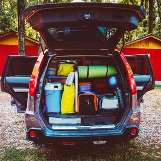 A car parked in front of a house packed with camping gear.