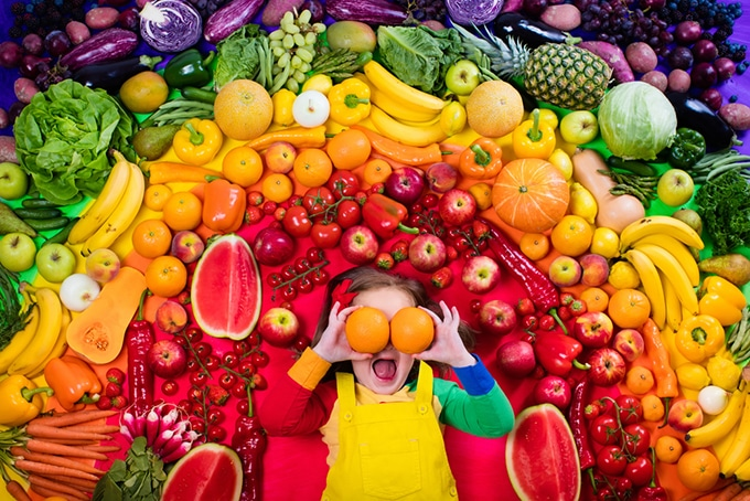 Child in front of a rainbow of vegetables.