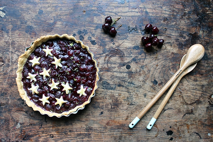 A homemade cherry pie with pastry stars on top, on a wooden table with fresh cherries.