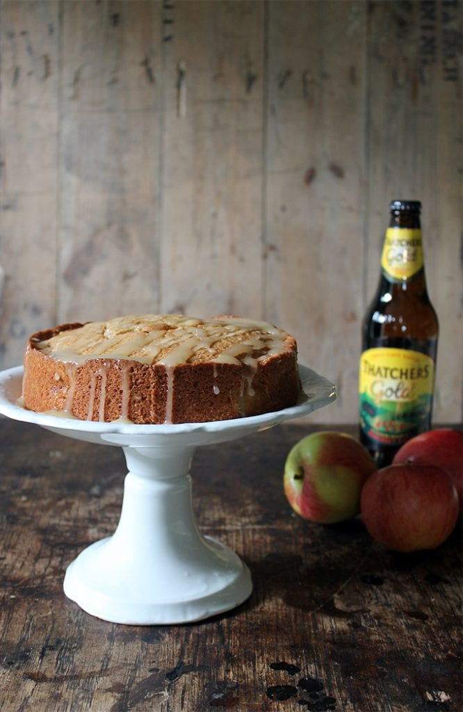 A cake on a cakestand, next to a bottle of cider.
