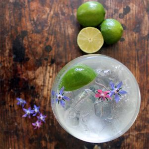 A glass of cocktail with edible flowers.